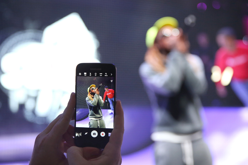 LOS ANGELES, CA - JUNE 14: A E3 Expo attendee takes a photo on a Samsung Galaxy S7 as rapper Lil Wayne performs onstage at the Samsung booth at E3 Expo 2016 on June 15, 2016 in Los Angeles, California. (Photo by Joe Scarnici/Getty Images for Samsung)