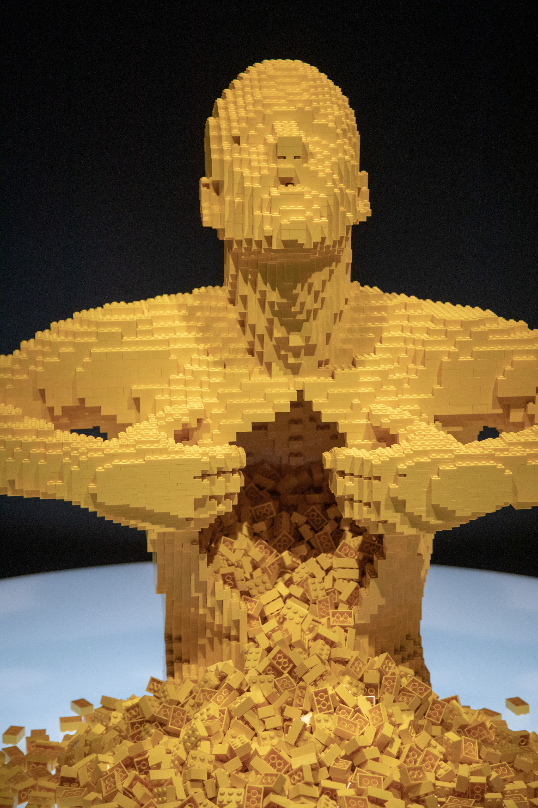 "The fan favorite Yellow is a life-size sculpture of a man ripping his chest open with thousands of yellow LEGO bricks cascading from the cavity. (Yellow has gained pop-culture fame appearing on fashion labels, album covers and even in Lady Gaga's music video ""G.U.Y."") (PHOTO CREDIT: JerSean Golatt/Perot Museum of Nature and Science)"